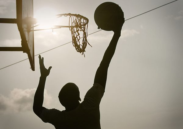 A young Cameroonian basketball player enjoys a pick-up game in Yaoundé, Cameroon, at Nlongkak basketball court, one of less than 10 outdoor courts throughout the city, on the evening of July 16.